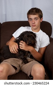 A teenage boy sitting on a couch with a dog.