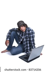 Teenage boy sitting on the floor with computer on white background