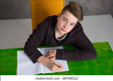 teenage boy sitting on green table and doing homework