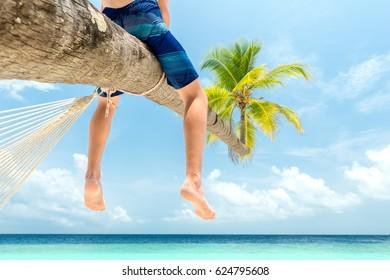teenage boy sitting on a palm tree at the beach