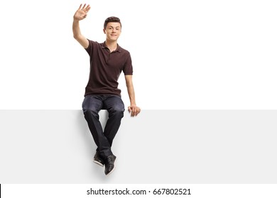 Teenage boy sitting on a panel and waving isolated on white background