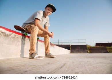 A teenage boy is sitting on a skateboard in the park and smiling