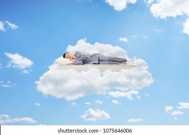 Teenage boy sleeping on a mattress up in the sky