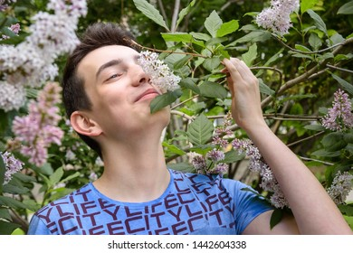 Teenage boy smelling lilac flowers in the park in summer