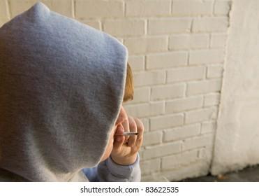 teenage boy smoking marijuana in grungy urban setting
