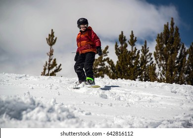 Teenage Boy snowboarding down steep snowy hill in the mountains