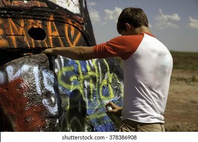 A teenage boy spray painting a car at Cadillac Ranch in Amarillo, Texas on July 13, 2015.