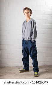 A Teenage boy, standing, hands in his pocket, making a cool confident face and pose.