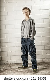 A Teenage boy, standing, hands in his pocket, making a cool confident face and pose. Picture Processed (See also natural version)
