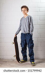A Teenage boy, standing, his skateboard in his hands next to him