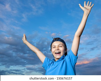 Teenage boy, standing outside, its evening, he is very happy, throwing his arms up in the air