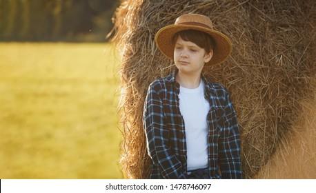 Teenage boy in straw hat standing near hay bale in a field, harvest concept.