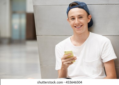 Teenage boy in street wear looking and smiling at the camera with cheerful expression while texting his friends via social networks using mobile phone, sitting against urban landscape background