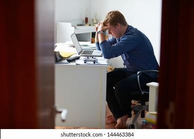 Teenage Boy Studying In Bedroom Using Laptop