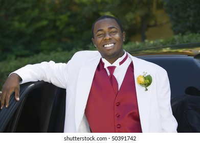 Teenage Boy in suit leaning on limo, portrait