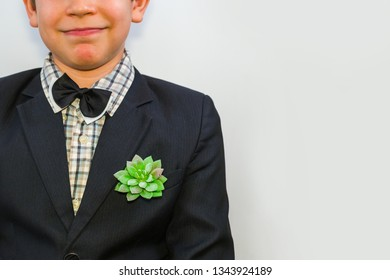 teenage boy in a suit. on pocket has plant flower. close up
