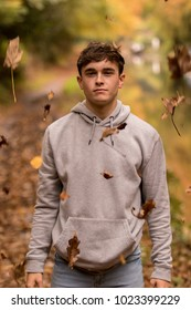 Teenage boy surrounded by falling leaves on an autumn day