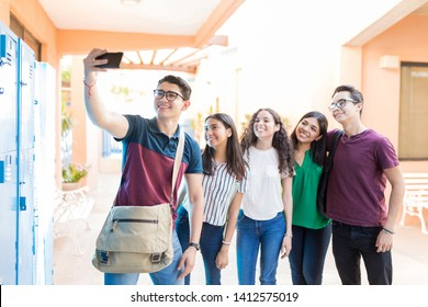 Teenage boy taking selfie with friends at university campus