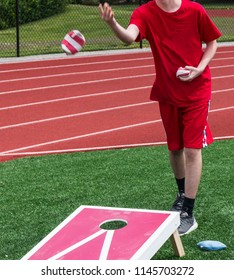 A teenage boy tosses a bean bag while playing corn hole in gym class on the turf with the track behind him.