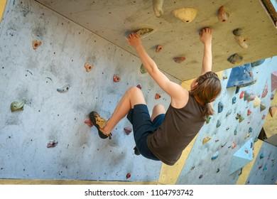 Teenage Boy Training Climbing On Indoor Climbing Wall