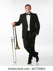 Teenage boy in tuxedo with trombone isolated