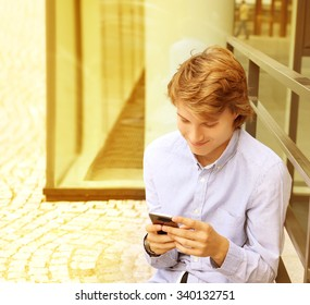 Teenage boy typing text message.Using smart phone