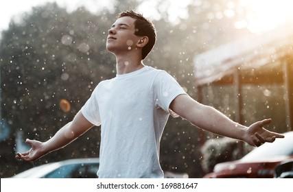 teenage boy under rain in the city