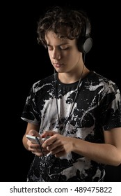 Teenage Boy Using Phone with headset, isolated on black