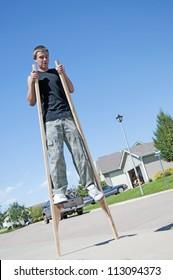 Teenage boy walking around the neighborhood on stilts.