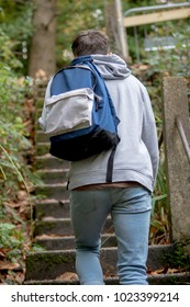 Teenage boy walking up outside concrete steps on an autumn day