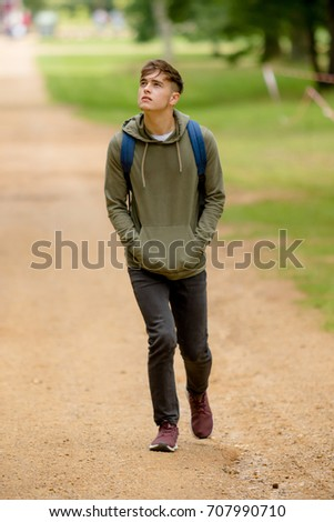 Teenage boy walking in a park on a summers afternoon