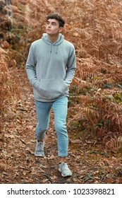 Teenage boy walking in the woods on an autumn day