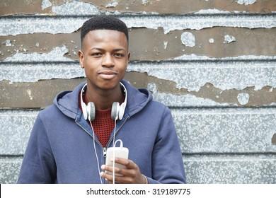 Teenage Boy Wearing Headphones And Listening To Music In Urban Setting