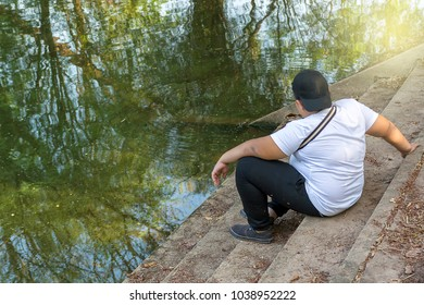 Teenage boy wearing white shirt Black pants and black hat, sit on a concrete ladder on the river, thinking, depressed, reckless