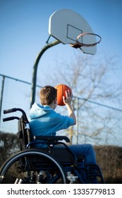 Teenage Boy In Wheelchair Playing Basketball Shooting Hoop