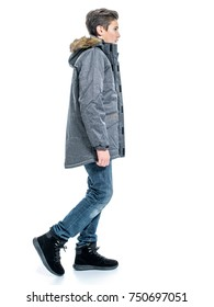Teenage boy in winter clothes - posing over white background. Young guy in gray warm jacket and boots