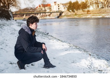 A teenage boy in a winter jacket but without a hat sits on the river bank in the snow and looks with faith as if into his future, asks God for a happy, full life and listens to the inner voice
