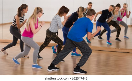 teenage boys and girls learning to dance in dance hall
