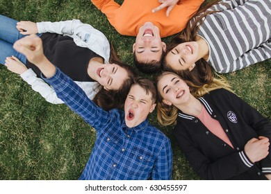 Teenage boys and girls lying in the grass on a summer holidays.