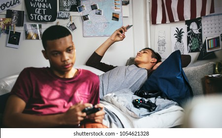 Teenage boys hanging out in a bedroom playing a video game and using a smartphone