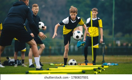 Teenage boys on football training session with two young coaches. Junior level soccer player kicking ball during practice session. Soccer training drills with hurdles agility