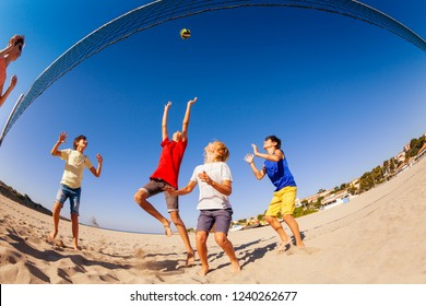 Teenage boys playing beach volleyball in summer