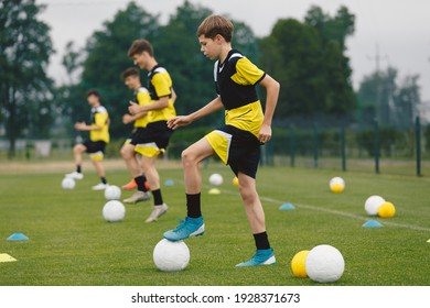 Teenage Boys Training Sports in a Row. Soccer Summer Camp for Young Boys. Happy Football Players on Practice Session. Youth Team Kicking Balls on Turf Pitch. Soccer Training Trail With Equipment