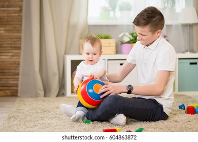 Teenage brother playing with his little sister