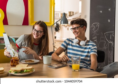 Teenage brother and sister watching the magazine while having breakfast at theirs home