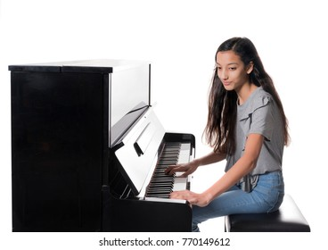 teenage brunette girl and black upright piano against white background in studio