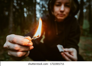 Teenage bully in hood holds burning match in his hand. Forest arsonist. Fire danger. Concept of arson and flame in night