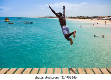 Teenage Cape verdean boy jumping on the turquoise  water of Santa Maria beach in Sal Cape Verde - Cabo Verde