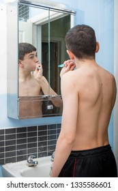 Teenage caucasian boy cleaning his teeth in the morning
