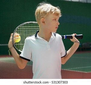 Teenage Caucasian boy holding a tennis racket and ball. Active and healthy lifestyle concept. Summer sport activities .